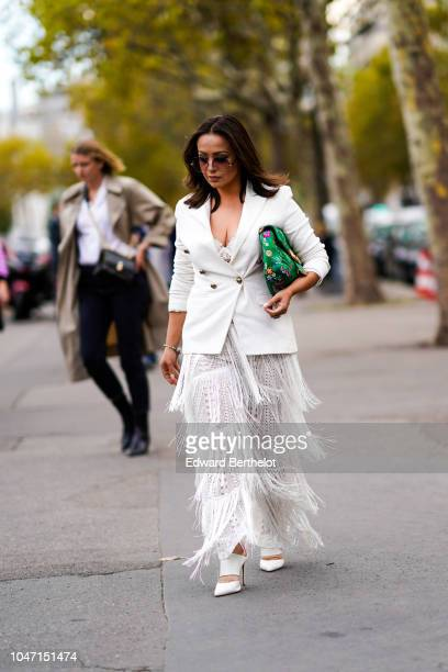 A guest wears a white blazer jacket a green floral print bag a white lace fringed dress outside Valentino during Paris Fashion Week Womenswear...