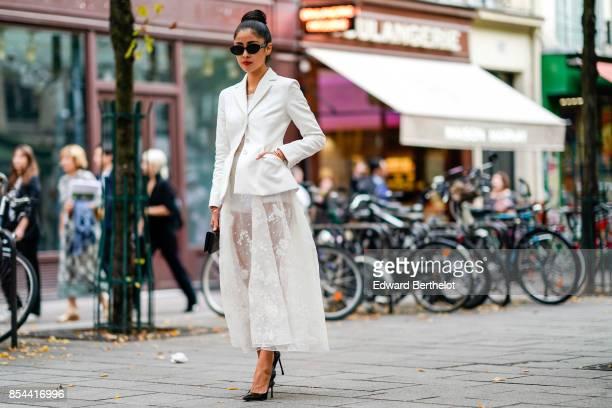 A guest wears a white blazer jacket a white lace mesh skirt black heels outside Koche during Paris Fashion Week Womenswear Spring/Summer 2018 on...