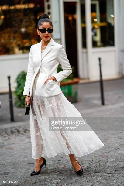 A guest wears a white blazer jacket a white lace mesh skirt black heels outside Koche during Paris Fashion Week Womenswear Spring/Summer 2018 on...