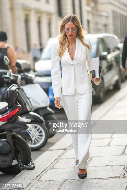 Guest wears a white blazer jacket, white flared suit matching pants, silver rings, a silver and diamond pendant necklace, black rhinestones with blue...