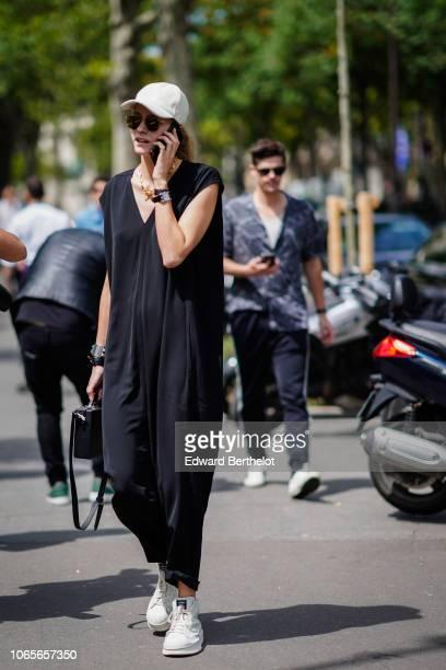 A guest wears a white cap a black long jumpsuit sneakers outside Rick Owens during Paris Fashion Week Menswear SpringSummer 2019 on June 21 2018 in...