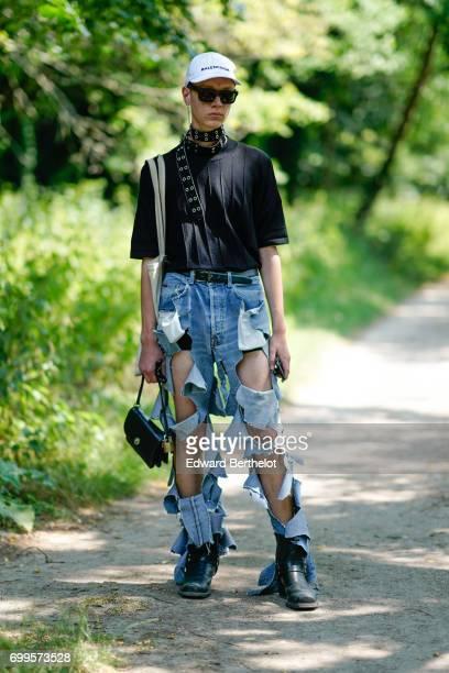 A guest wears a white cap a black top ripped blue denim jeans pants a black bag outside the Balenciaga show during Paris Fashion Week Menswear...