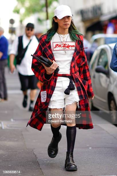 A guest wears a white cap a red and black checked jacket a white tshirt with printed logo white shorts black shoes outside Yohji Yamamoto during...