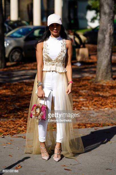 A guest wears a white cap a white outfit a pink bag with embroidery a lace dress outside Issey Miyake during Paris Fashion Week Womenswear...