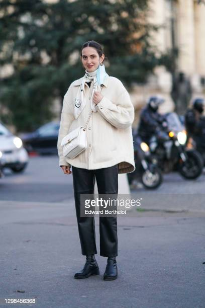 Guest wears a white Chanel scarf, a white wool oversized jacket, a white quilted leather Chanel bag, black leather pants, black leather boots,...