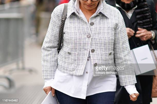 A guest wears a white Chanel shirt a white Chanel crop jacket outside the Chanel Cruise Collection 2020 At Grand Palais on May 03 2019 in Paris France