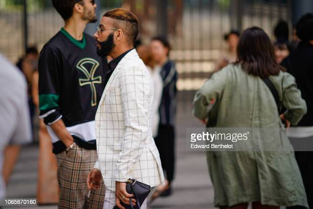 A guest wears a white checked blazer jacket outside Issey Miyake during Paris Fashion Week Menswear SpringSummer 2019 on June 21 2018 in Paris France