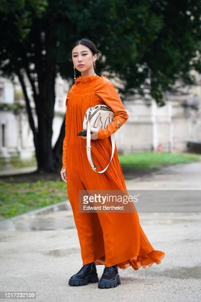 Guest wears a white Chloe bag, earrings, an orange pleated and ruffled long dress, black leather boots, outside Chloe, during Paris Fashion Week -...