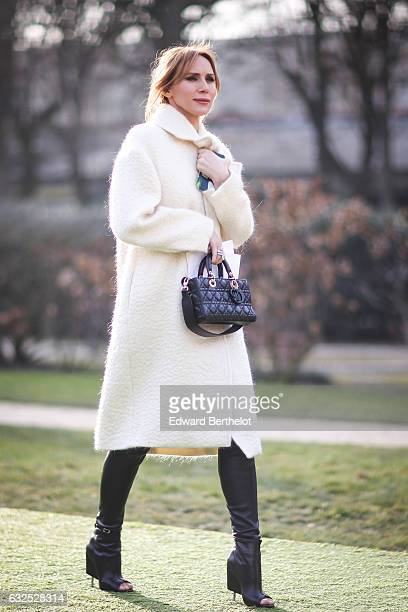 A guest wears a white coat a black Dior bag and attends the Christian Dior Haute Couture Spring Summer 2017 show as part of Paris Fashion Week at the...