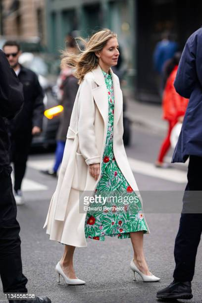 Guest wears a white coat, a green floral print dress, white pointy high-heeled pumps, outside Thom Browne, during Paris Fashion Week Womenswear...