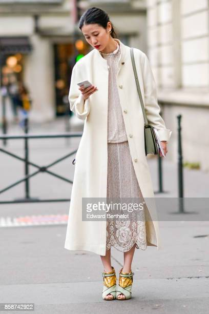 A guest wears a white coat a lace dress outside Valentino during Paris Fashion Week Womenswear Spring/Summer 2018 on October 1 2017 in Paris France