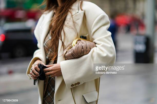A guest wears a white coat a Miu Miu bag outside Miu Miu during Paris Fashion Week Womenswear Spring Summer 2021 on October 06 2020 in Paris France