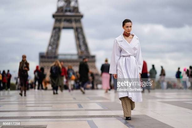 Guest wears a white coat, Gucci pants, outside Hermes, during Paris Fashion Week Womenswear Spring/Summer 2018, on October 2, 2017 in Paris, France.