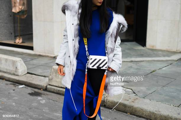 A guest wears a white coat with fur purple pants an OffWhite bag during Paris Fashion Week Womenswear Fall/Winter 2018/2019 on March 1 2018 in Paris...