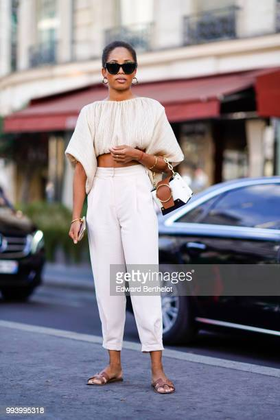 A guest wears a white cropped bare belly top white pants sunglasses earrings outside Fendi during Paris Fashion Week Haute Couture Fall Winter...