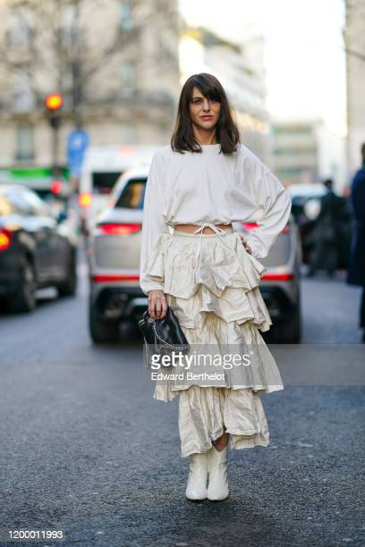 A guest wears a white cropped top a white ruffled skirt white boots a black bag outside Rochas during Paris Fashion Week Menswear Fall / Winter...