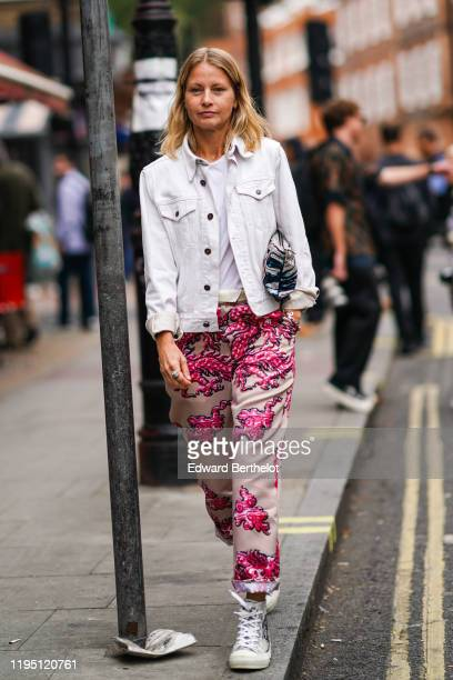 Guest wears a white denim jacket, pants with pink floral print, sneakers shoes, a bag, outside JW Anderson, during London Fashion Week September 2019...