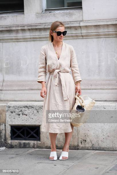 A guest wears a white dress a basket bag sunglasses white shoes outside JeanPaul Gaultier during Paris Fashion Week Haute Couture Fall Winter...