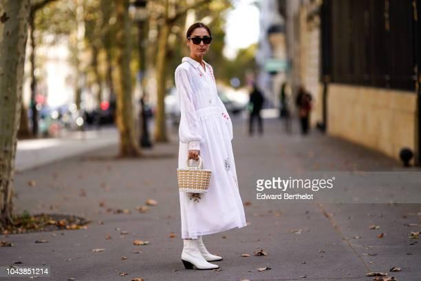 Guest wears a white dress, a basket bag, white shoes, outside Altuzarra, during Paris Fashion Week Womenswear Spring/Summer 2019, on September 29,...