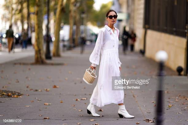 Guest wears a white dress, a basket bag, white shoes, outside Altuzarra, during Paris Fashion Week Womenswear Spring/Summer 2019, on September 29,...