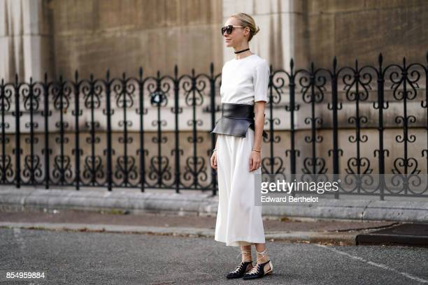 A guest wears a white dress a black corset shoes outside the Dries Van Noten show during Paris Fashion Week Womenswear Spring/Summer 2018 on...