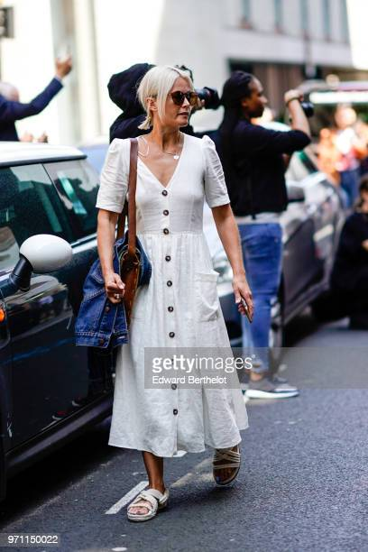A guest wears a white dress a brown bag sandals during London Fashion Week Men's June 2018 on June 10 2018 in London England