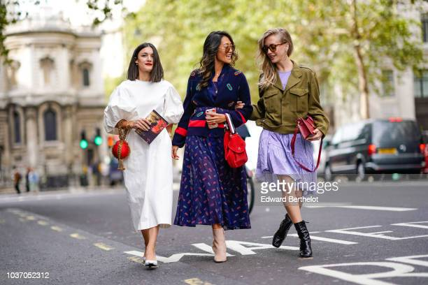 A guest wears a white dress a guest wears a blue skirt a guest wears a green jacket during London Fashion Week September 2018 on September 14 2018 in...