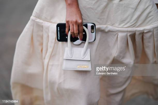 A guest wears a white dress a Jacquemus mini bag holds a mobile phone with a Karl Lagerfeld phone case during London Fashion Week Men's June 2019 on...