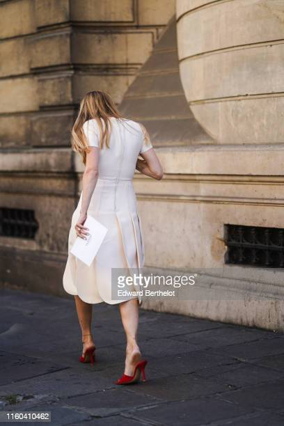 A guest wears a white dress and red shoes outside Valentino during Paris Fashion Week Haute Couture Fall/Winter 2019/2020 on July 03 2019 in Paris...