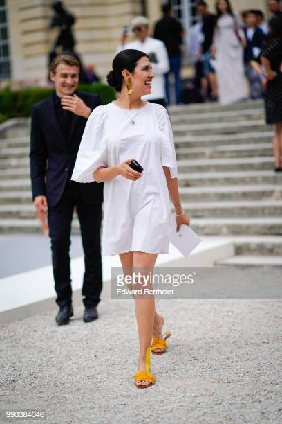 A guest wears a white dress outside Dior during Paris Fashion Week Haute Couture Fall Winter 2018/2019 on July 2 2018 in Paris France