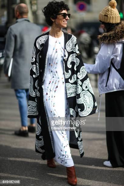 A guest wears a white dress outside the Miu Miu show during Paris Fashion Week Womenswear Fall/Winter 2017/2018 on March 7 2017 in Paris France