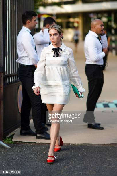 Guest wears a white dress with a black bow collar, red Miu Miu Mary Jane pumps, outside Miu Miu Club 2020, on June 29, 2019 in Paris, France.