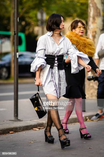 A guest wears a white dress with a black corset a black bag black kneehigh tights and black platform shoes a guest wears yellow sunglasses a collar...