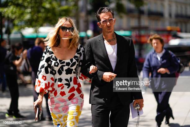 A guest wears a white dress with colored printed features a guest wears sunglasses a white tshirt a blazer jacket outside Louis Vuitton during Paris...