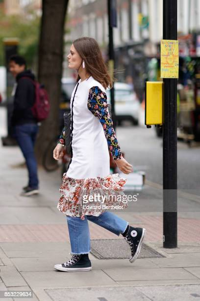 A guest wears a white dress with colored sleeves jeans Converse shoes a lace skirt outside JW Anderson during London Fashion Week September 2017 on...