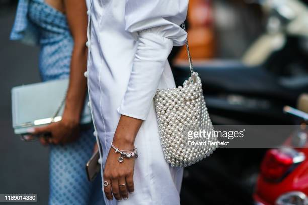 A guest wears a white dress with legofmutton sleeves a pearl woven beadwork bag outside the Bottega Veneta show during Milan Fashion Week...