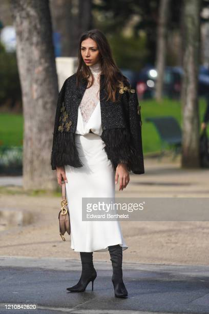 Guest wears a white dress with mesh parts, a black jacket with fluffy fringed parts, a Dior bag, pointy high heeled shoes, outside Chanel, during...