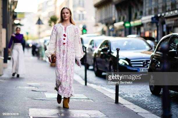 A guest wears a white dress with pink embroidery outside Valentino during Paris Fashion Week Haute Couture Fall Winter 2018/2019 on July 4 2018 in...