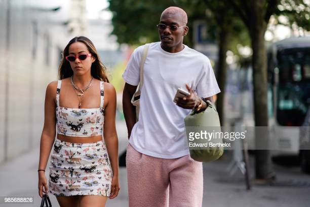 A guest wears a white dress with printed animal drawings a guest wears a white tshirt pink pants a green bag outside 1017 ALYX 9SM during Paris...