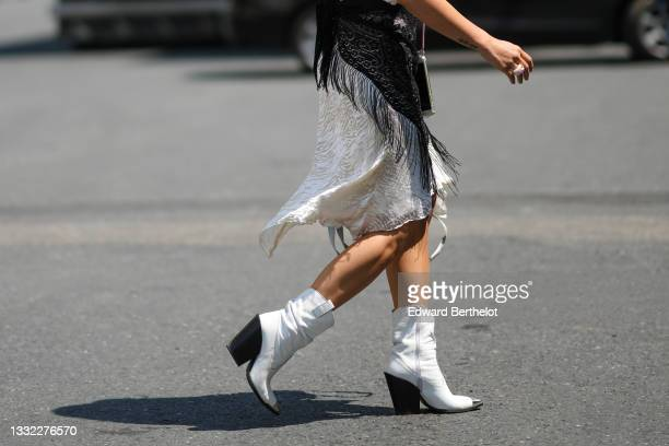 Guest wears a white embossed / ruffled beige print pattern long asymmetric knees dress, a black lace fringed knotted scarf, a gold chain with white...