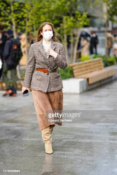 Guest wears a white face mask, a beige checked blazer jacket, a brown leather belt, a brown suede skirt, beige boots, outside Louis Vuitton, during...