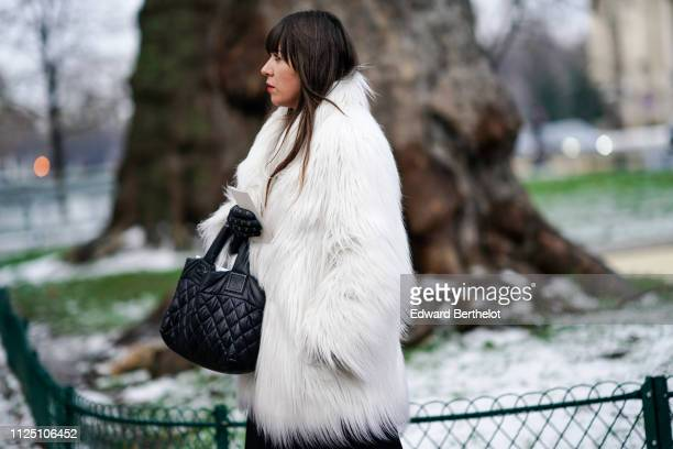 A guest wears a white faux fur coat and a black leather Chanel bag outside Alexandre Vauthier during Paris Fashion Week Haute Couture Spring Summer...