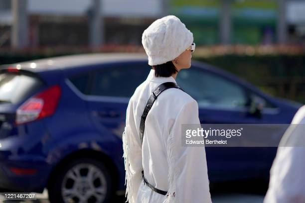 A guest wears a white fluffy hat a white jacket with fringes outside Gucci during Milan Fashion Week Fall/Winter 20202021 on February 19 2020 in...