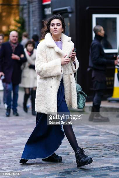 Guest wears a white fluffy long coat, a purple pullover, a blue skirt, black tights, black sneakers, earrings, during London Fashion Week Men's...