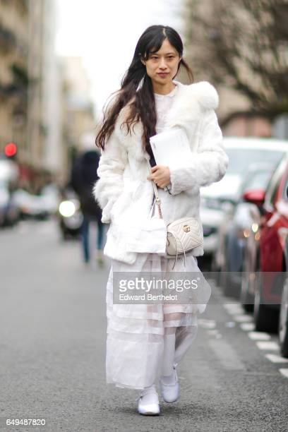 A guest wears a white fur coat and a lace dress outside the Moncler show during Paris Fashion Week Womenswear Fall/Winter 2017/2018 on March 7 2017...
