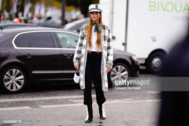 A guest wears a white hat a black and white checked coat black pants outside Chanel during Paris Fashion Week Womenswear Spring/Summer 2019 on...