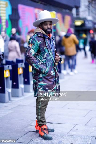 A guest wears a white hat a military camouflage coat green khaki pants orange shoes during London Fashion Week Men's January 2018 at on January 6...