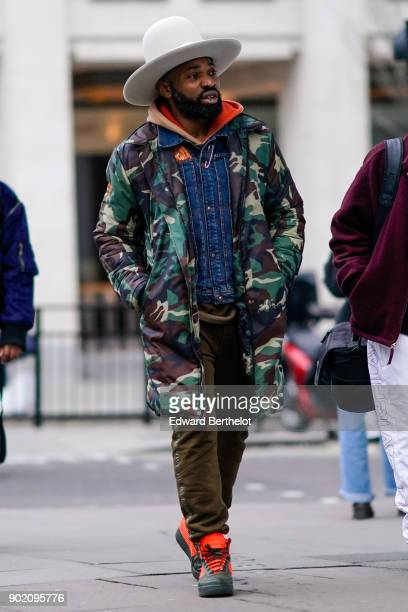 A guest wears a white hat a military camouflage print jacket a hoodie top pants orange sneakers during London Fashion Week Men's January 2018 at on...