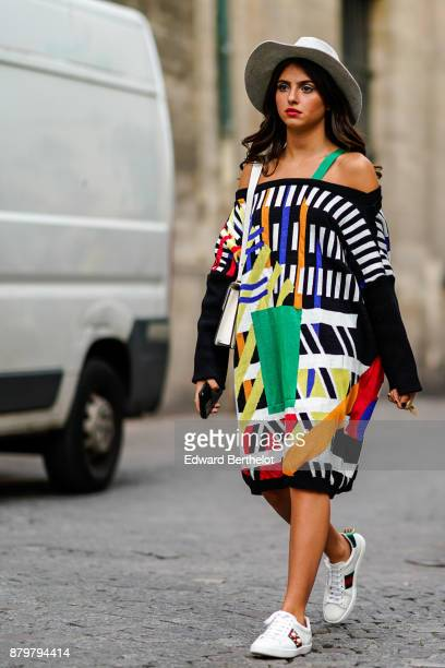 A guest wears a white hat an offshoulder colored dress white sneakers outside Koche during Paris Fashion Week Womenswear Spring/Summer 2018 on...