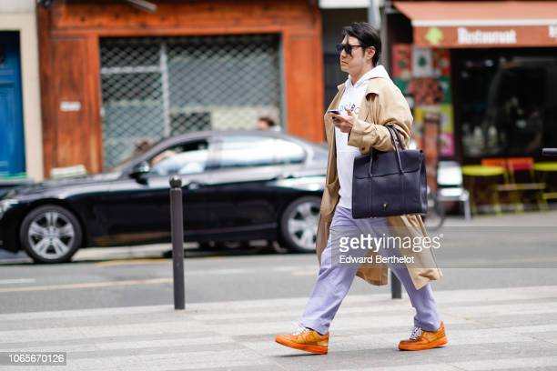 A guest wears a white hoodie sweater a balck bag a beige jacket blue and white pants orange sneakers shoes outside Issey Miyake during Paris Fashion...